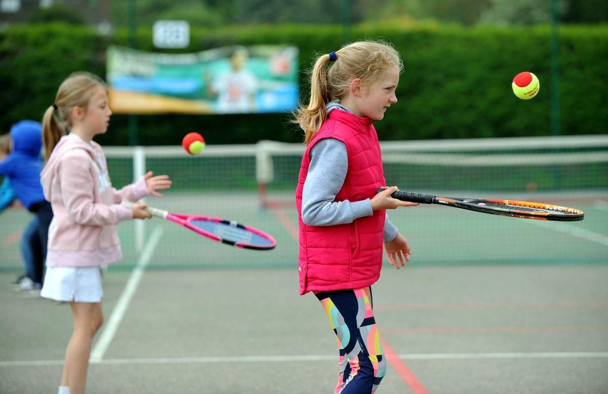 Girls in tennis coaching session