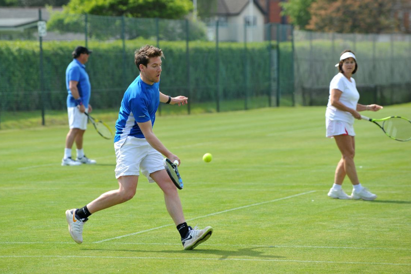 People playing grass court tennis